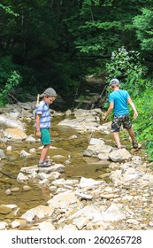 Two kids playing near a mountain stream