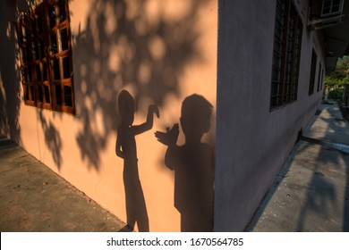 Two kids playing with shadow of a morning light.