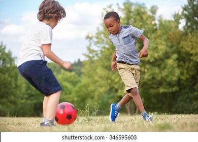 Two kids playing soccer in summer