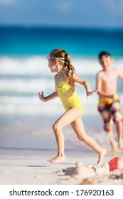Two kids playing at tropical beach during summer vacation