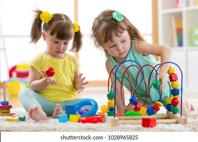 Two kids playing with wooden blocks in their nursery room