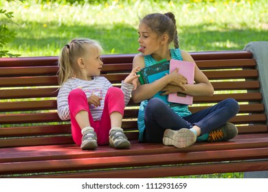 Two kids quarrel on a bench in the park. The older sister does not want to share books with a younger and puts out one's tongue