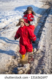 Two kids in rainboots running together on the ice puddle at sunny spring day, outdoors