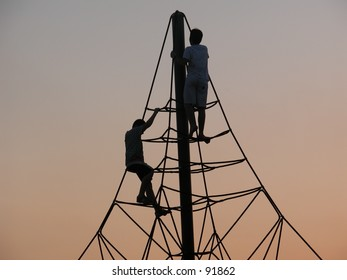 Two kids reaching the top of a climbing structure