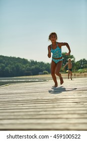 Two kids running and playing on a pier at the lake on the summer holidays