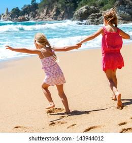 Two kids running towards water at seaside.