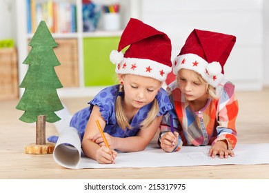 Two kids with santa hats writing wishlist while lying on the floor