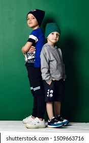 Two kids schoolboy and preschooler in modern sportswear knitted hats, pants, shorts, hoody and t-shirt cool posing back to back with hands in their pockets and crossed on green