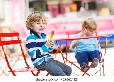 Two kids - sibling boys eating colorful ice cream in summer, outdoors. Selective focus.