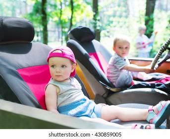Two kids sit in car. One kid drives family car.