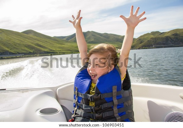 Two kids sitting in the bow of a boat with there life jackets having fun
