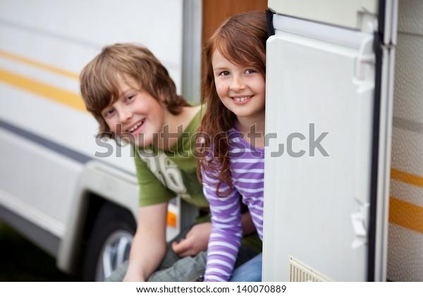 Two Kids Sitting In Doorway Of RV
