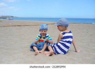 Two kids sitting on the beach