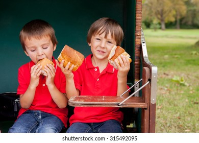 Two kids, sitting in a sheltered bench, eating sandwiches, outdoor summertime