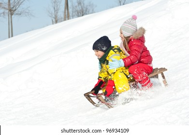 Two kids sliding with sledding in the snow.