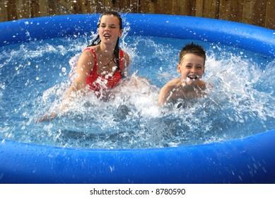 Two kids splashing in pool.
