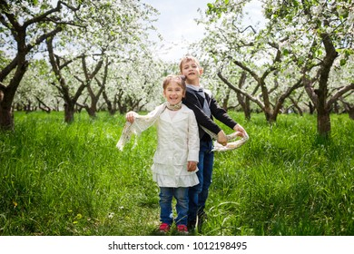 Two kids in spring garden with blooming apple and cherry tree.
