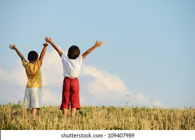 Two kids standing on meadow with arms up in air