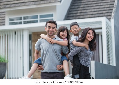 two kids with their parent having fun together in front of their new house. piggyback ride