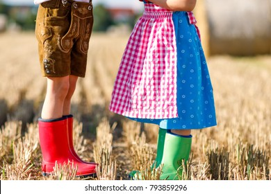 Two kids in traditional Bavarian costumes and red and green rubber boots in wheat field. German children during Oktoberfest . Boy and girl at hay bales during summer harvest time. Close-up of legs