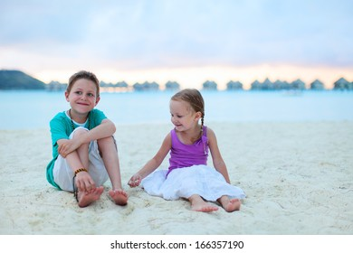 Two kids at tropical vacation resort beach