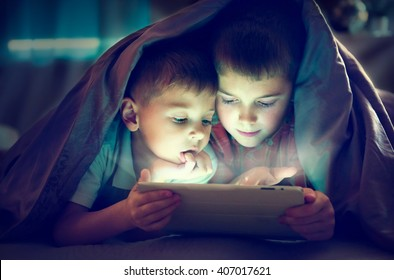 Two kids using tablet pc under blanket at night. Brothers with tablet computer in a dark room