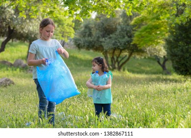 Two kids volunteer charity environment.Children with garbage bags cleaning up polluted environmental rubish in forest.