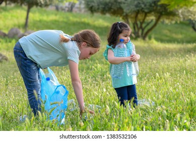 Two kids volunteer cleaning plastic pollution in summer park. Children with garbage bags cleaning up polluted environmental rubish in forest.