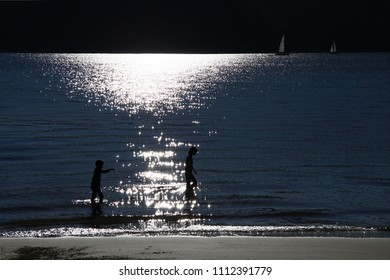 Two kids walking in the sun drenched water at the beach and sail boats passing by on the horizon.