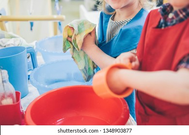 Two kids washing dishes. Montessori engaging educational activities concept. Children cleaning tableware.