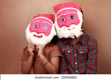 Two kids wear hand made masks of Santa