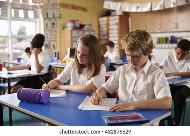 Two kids working at desks in a primary school classroom