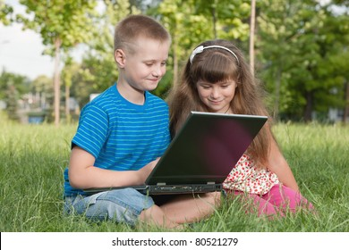 Two kids are working on a laptop outdoors on the grass