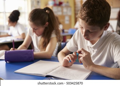Two kids working at their desks in primary school, close up