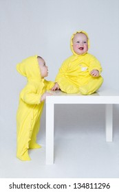 Two kids in yellow suits