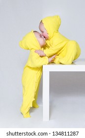 Two kids in yellow suits embrace.One sits on a small little table, another stands nearby.