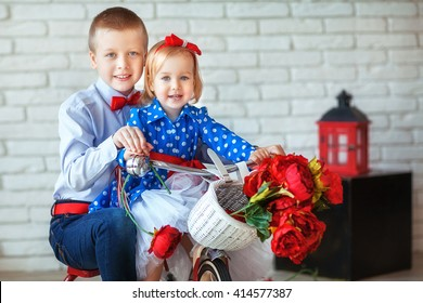Two kids,happy teenager boy and his cute toddler sister.Fashion laughing children biking indoor.Pretty little girl in a blue dress and his brother on a red bicycle with red roses in a basket