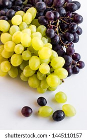 Two kinds of grapes on the white surface.