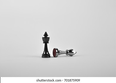 Two king chess pieces on a white background with one fallen.