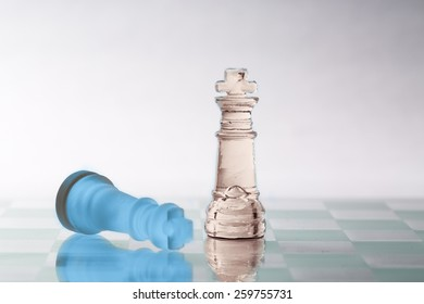 Two kings from a glass chess set on a glass board.  One is blue and the other is a pale copper.  One piece is standing and one is laying down.