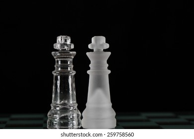 Two kings from a glass chess set side by side on black background/