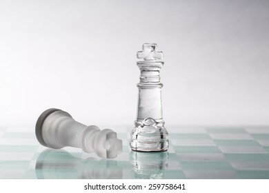 Two kings from a glass chess set on a glass board.   One piece is standing and one is laying down.