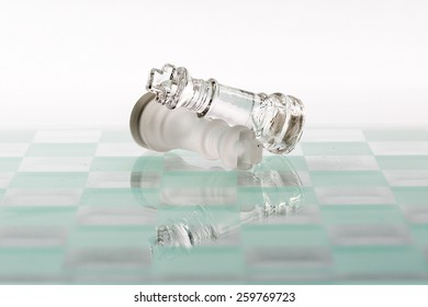 Two kings from a glass chess set laying on each other on a glass chess board.  White background.