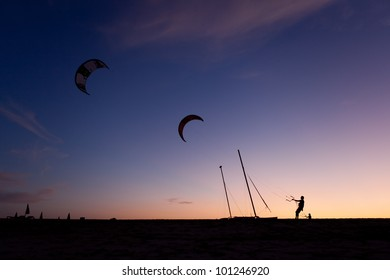 Two kiteboarders in the sunset