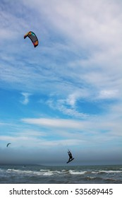 Two kiters are on the waves, one of them is jumping with bright colorful kite against blue sky with white clouds on the Black sea in Odessa Ukraine