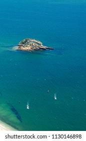 Two kitesurfers, seen from far and above, surfing over blue and green waters facing Portinho da Arrabida beach at Serra da Arrabida. Small island in view. Setubal, Portugal.