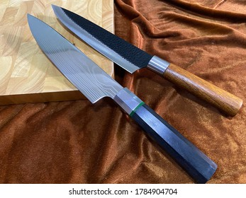 Two knifes and wood cutting board on brown background