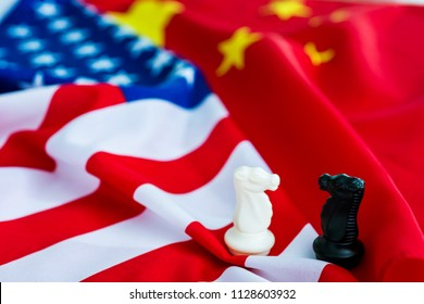Two knight chess pieces standing on american flag and china flag.
