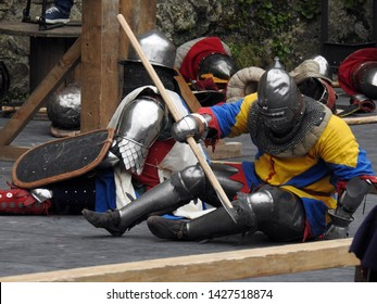 Two knights in full plate armour in the aftermath of battle still seated inside an arena with one of them holding a battleaxe getting up on feet. Old castle wall and equipment in the background
