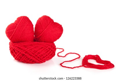 Two knitted hearts in a nest from threads on white background